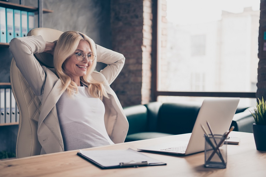 Photo of excited cheerful ecstatic woman working in front of her laptop with project finished and salary received according to annual income